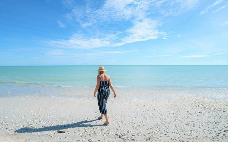 Person on beach walking towards water