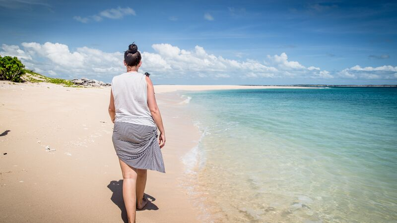 Woman walking in a white sand beach with turquoise water.