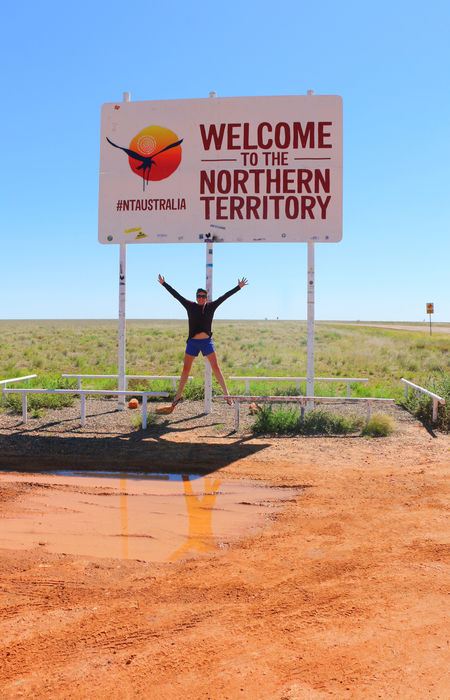 person jumping in front of the northern territory welcome sign
