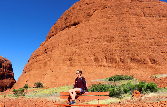 Person sitting on a bench in the outback of australia in front of red rocks