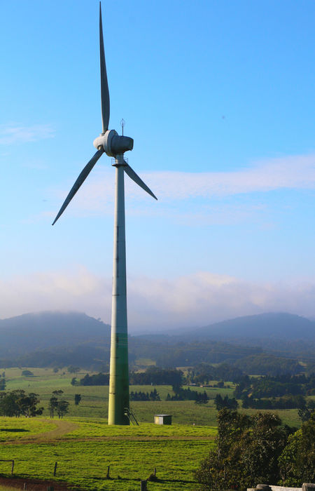 Tall wind farm set against green hills and blue sky