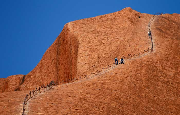 Three men climbing Uluru