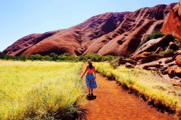 Girl in floral skirt walks towards Uluru