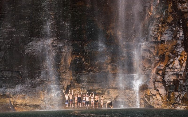 People standing under a waterfall