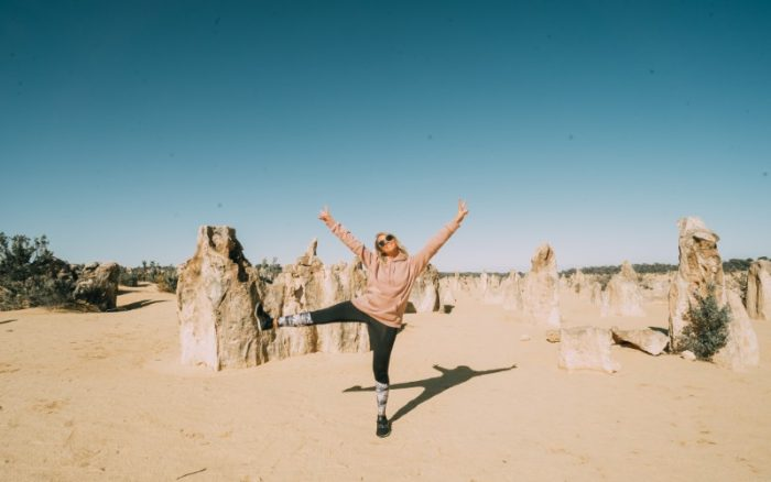 Person doing a star jump in front of the Pinnacles