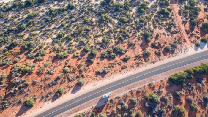 Drone footage from above a desert highway with red sand and green trees each side of the road