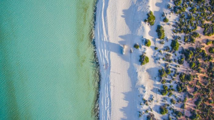 Done footage of Shark Bay with water on the left and beach on the right looking from above