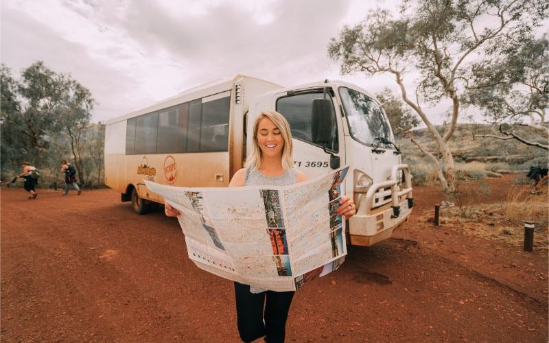 Person holding a map in front of a truck in the outback