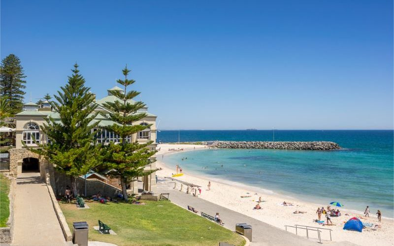 Image of the beach in Perth with blue sky and white sand and a few trees.